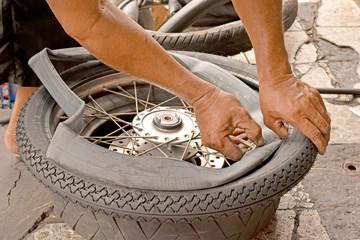 Motorcycle mechanic changing a wheel.