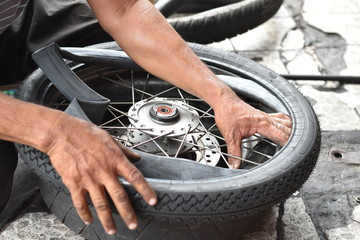 Motorcycle mechanic changing a wheel.