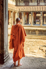 Fototapete - Buddhist monk exploring courtyards of Angkor Wat in Cambodia