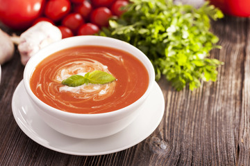 Delicious tomato soup with aromatic spices on a wooden table.