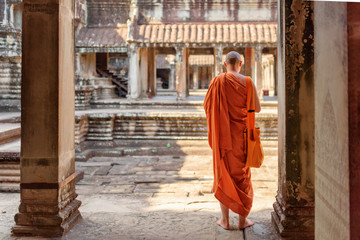 Wall Mural - Buddhist monk exploring courtyards of Angkor Wat in Siem Reap