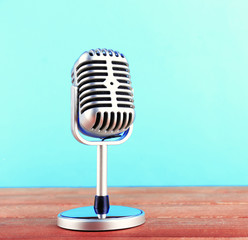 Retro microphone on wooden table on turquoise background