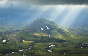 Fotomurales - Sun breaking through the clouds on a mountain on the Laugavegur hiking trail on Iceland.