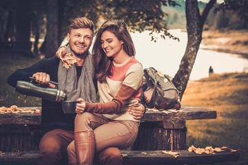 Cheerful couple with hot drink in autumn park