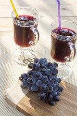 Grape juice cooler with ice in glass and glass of fresh blue grapes on a wooden table close-up, selective focus