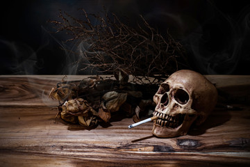 Still life Smoking human skull with cigarette on wooden table, p