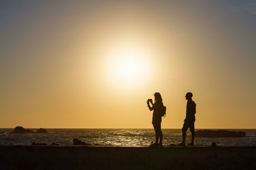 Silhouette of couple taking pictures by the sea