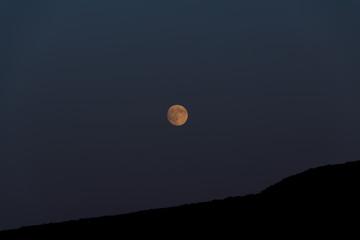 Big moon shines over the mountain. Night