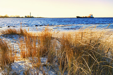 The ship enters the harbor lighthouse in winter