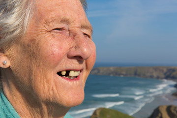 Old lady pensioner with dental problems and tooth missing by coast scene