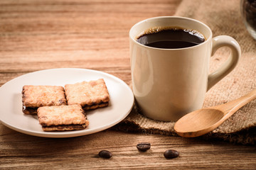 Coffee cup and saucer with cracker on a wooden table.