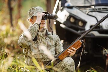 hunter with shotgun looking through binoculars in forest