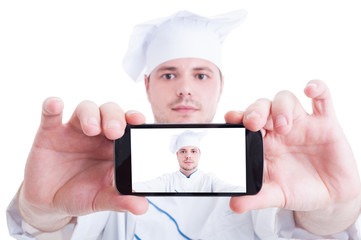 Chef or cook taking selfie with back phone camera