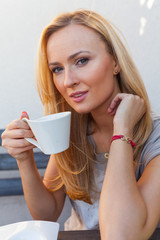 A pretty caucasian woman at home sitting on the porch and drinking coffee.