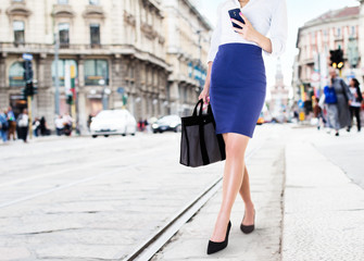 A business woman with smart phone walking in the street. Beautiful legs with office fashion. bag and dhoes in the city.