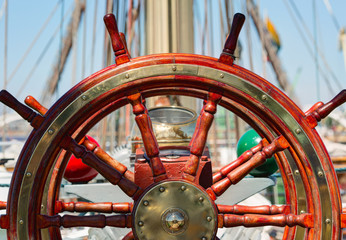 Wooden lacquer steering wheel of the sailboat.