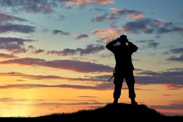 Silhouette of soldier looking through binoculars