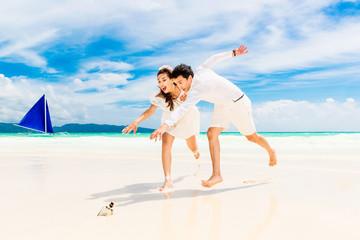 Happy Bride and Groom having fun on the tropical beach. Wedding