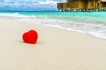 Red heart rendered ashore from the ocean.