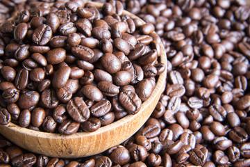 roasted coffee beans in wooden bowl with coffee background