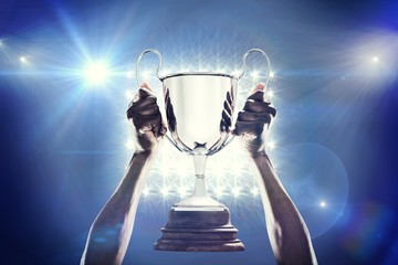 Composite image of cropped hand of athlete holding trophy Wall mural