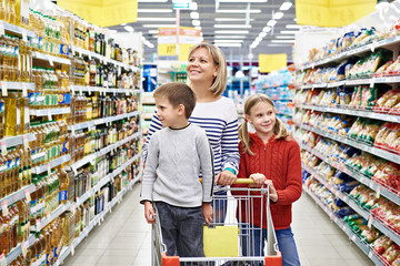 Women and children with cart shopping in supermarket
