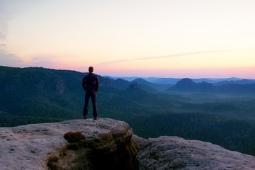 Hiker stand on the cliff of sandstone rock empire and watch over the misty and foggy morning valley