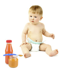 Cute baby boy and baby food in jars isolated on white