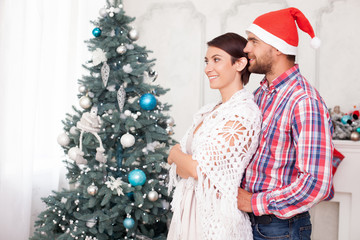 Pretty husband and wife are resting near Christmas tree