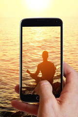 Male hand taking photo of man meditating in lotus pose on the beach near the sea, ocean, during sunset with cell, mobile phone.