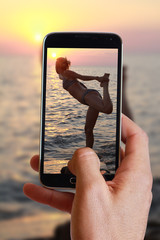 Male hand taking photo of woman meditating on the beach near the sea, ocean, during sunset with cell, mobile phone.