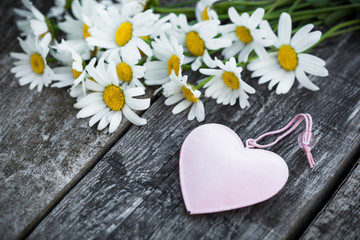 Beautiful fresh daisies decorated with hearts on wooden texture
