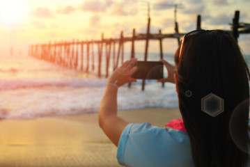 Blur woman using smart phone take picture on sunset beach