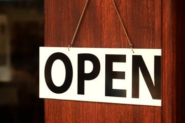 Open sign broad hanging on wooden door in street cafe.
