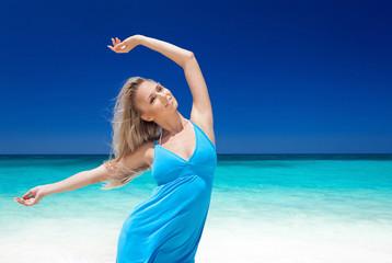 Happy blond girl on beach, feeling freedom.