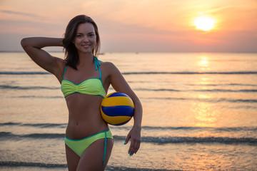 sexy sporty woman in bikini with ball over sea background