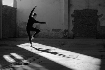 Young modern dancer exercising and dancing in abandoned building.