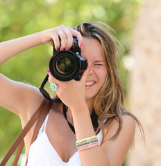 Happy woman photographer holding a dslr camera