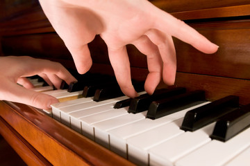 Close-up of a pianist playing the piano with both hands.