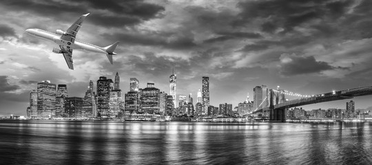 Black and white view of airplane overflying New York City