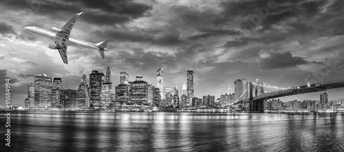 Wall mural Black and white view of airplane overflying New York City