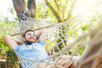 caucasian man using mobile phone white swinging in a hammock