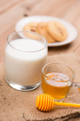 glass of milk with honey and cookie