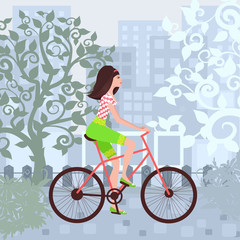 Beautiful girl is riding on a bicycle in a city.