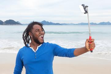 Mann mit Rastalocken am Strand macht Selfie