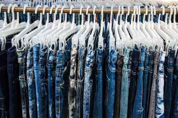 Row of Jeans and trousers on hangers for sale