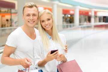 Positive couple holding packages