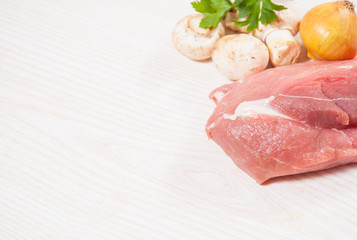 Food background of fresh meat, mushrooms, onion at the wooden board with copy space