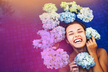 dramatic portrait of a woman floating an a swimming pool full of flowers