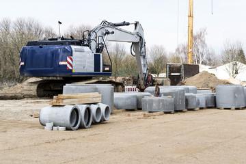 Blauer Bagger und Betonrohre auf einer Großbaustelle